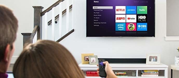 A flat-screen TV with the Roku screen and the back of two model's head, with one holding up a remote to the TV
