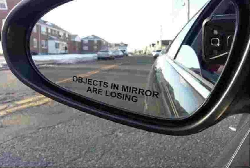 """A close up of a car's side mirror with the sticker, """"objects in mirror are losing."""""""
