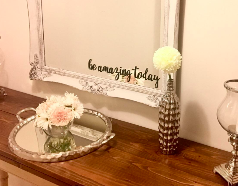 """The wall decal that reads, """"be amazing today"""" placed on a mirror."""