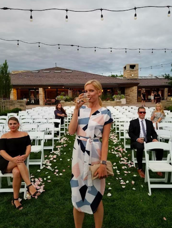 Reviewer wearing the knee-length dress with a tie around the waist and a geometric pattern in white, pink, light blue, and navy blue.