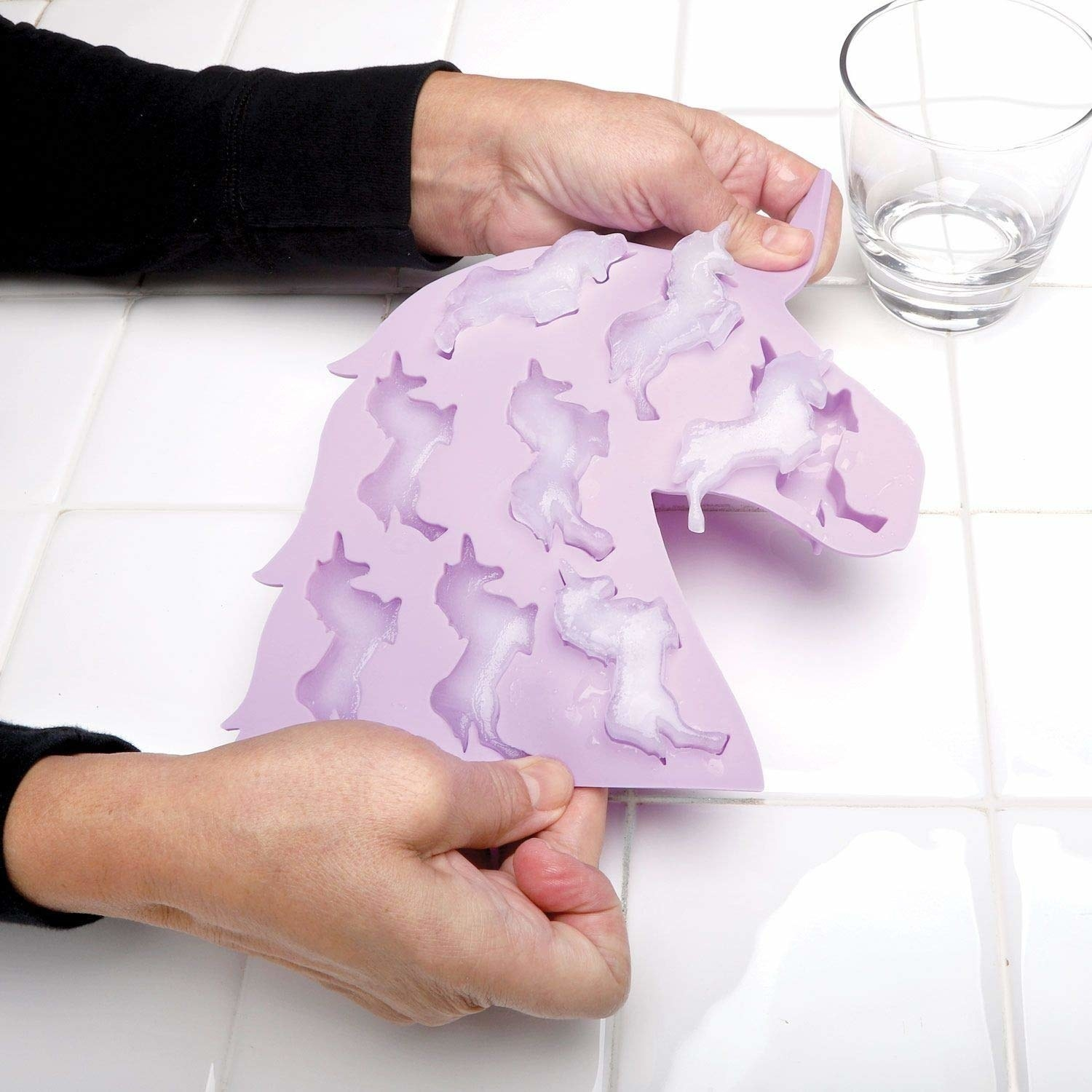 hands remove ice from unicorn ice making tray shaped like unicorn head