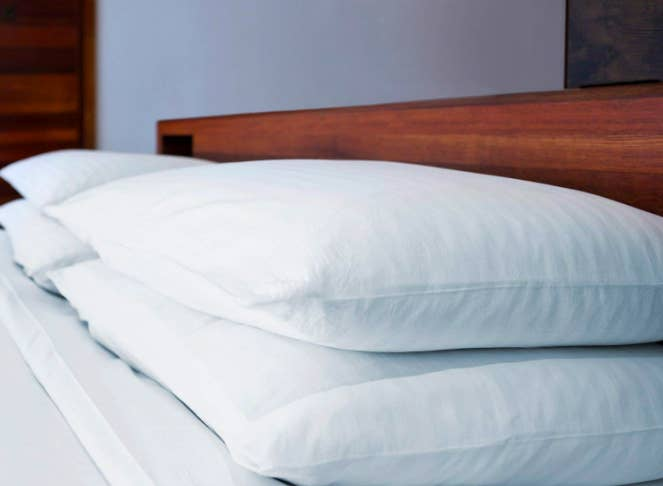 A lifestyle shot of four low-loft pillows, two on each side of the bed