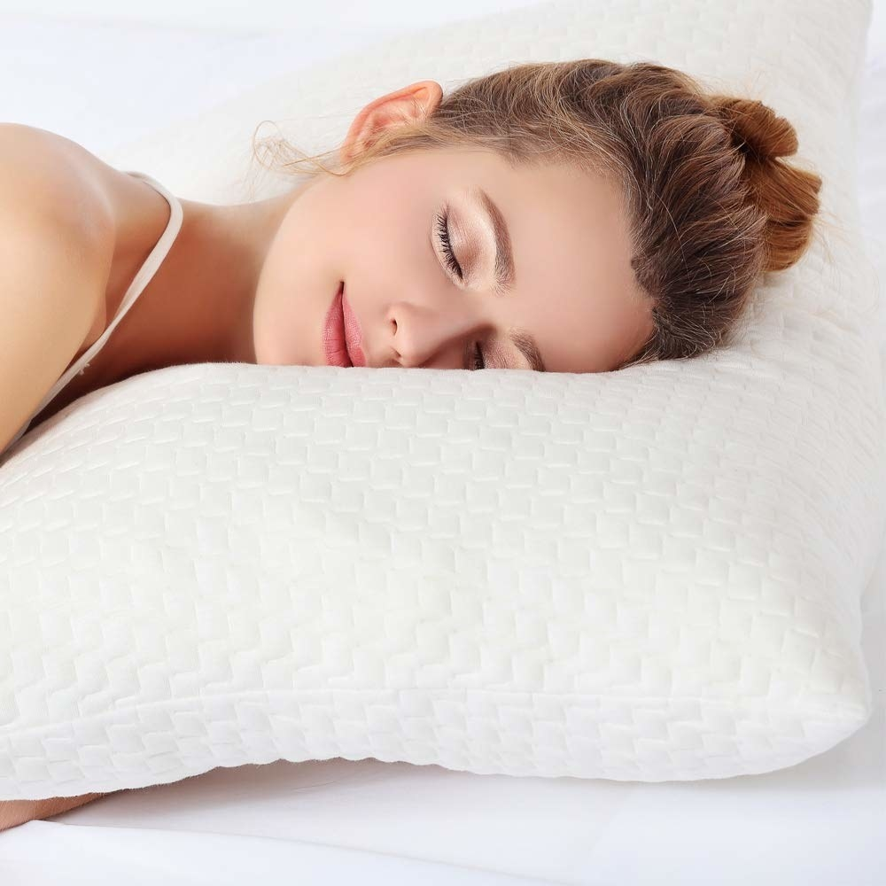 A model sleeping on the pillow, their hands are beneath while they sleep on their side. The pillow is high loft and flexible in the image.