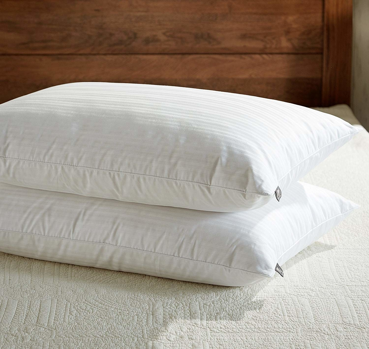 A product shot showing two of the pillows, one stacked on the other. The material is a standard white with light stripes.