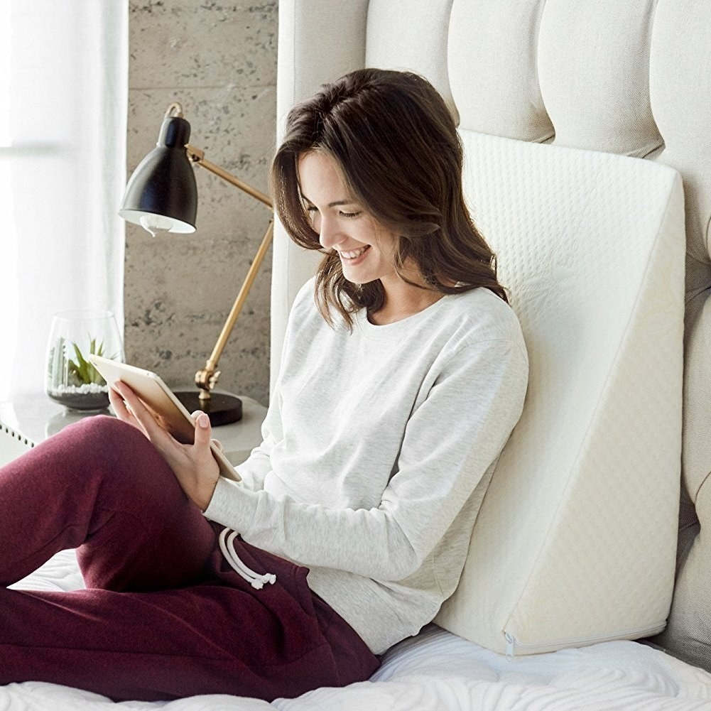 A model sitting up in bed and reading while using the triangular pillow as lower back support