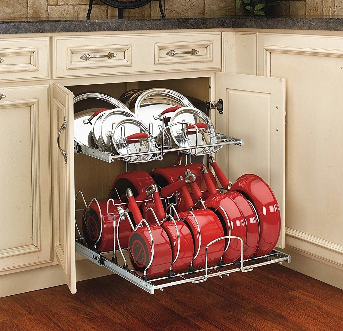 The metal organizer with nine pots/pans on the bottom and lids on top