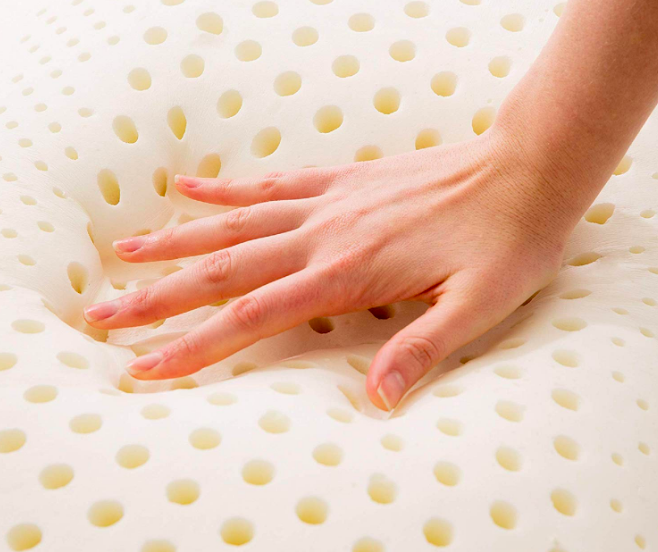 A model's hand pressing against the pillow, creating a deep shape where their hand was to show the forming memory foam. The pillow has holes throughout it for structure and circulation.