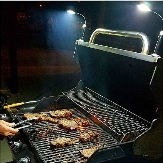 a model grills at night with two lights connected to the top of the grill