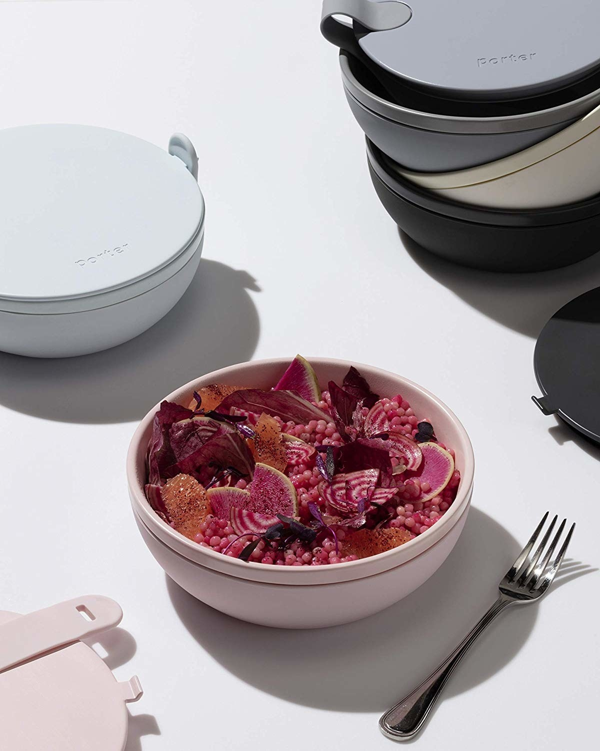 round pink bowl with a lid next to it and a silicone strap across the top