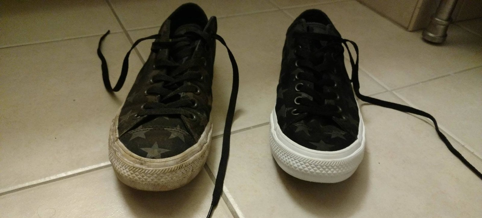 A reviewer's pair of sneakers: one with very dirty soles and sides and the other looking basically brand new white