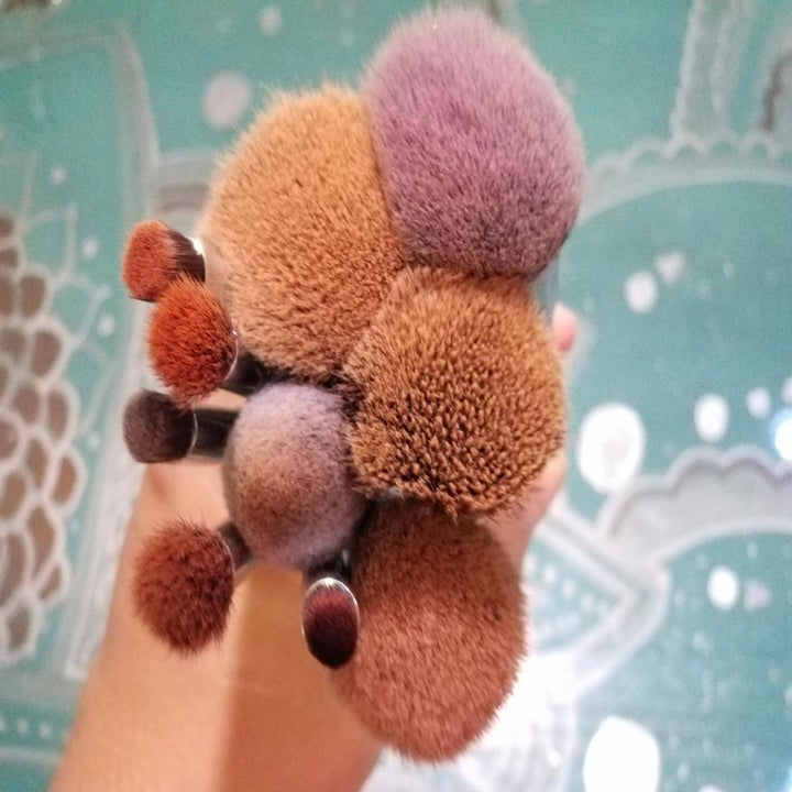 A reviewer's before image of a bunch of makeup brushes stained orange and pink