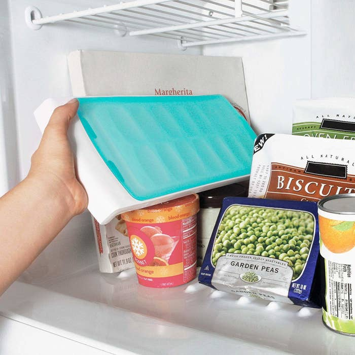 model puts ice tray with lid into freezer sideways