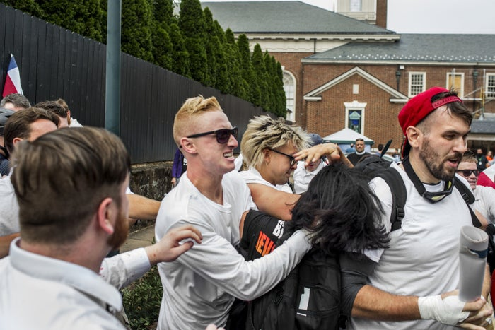 """Rise Above Movement member Ben Daley (center) attacks a woman at the """"Unite the Right"""" rally on Aug. 12, 2017, in Charlottesville, Virginia. Another RAM member, Michael Miselis, is in the baseball cap."""