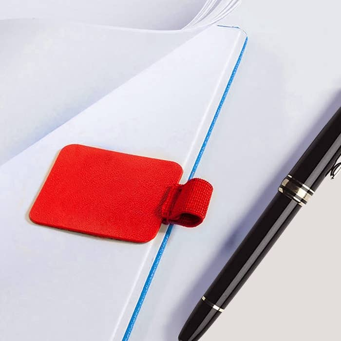rectangle sticker with loop for pen attached to notebook