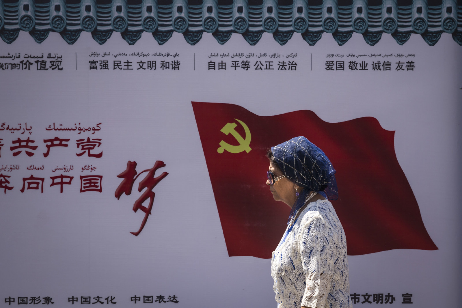 A Uighur woman passes the Communist Party of China flag on the wall on June 27, 2017, in Ürümqi, China.