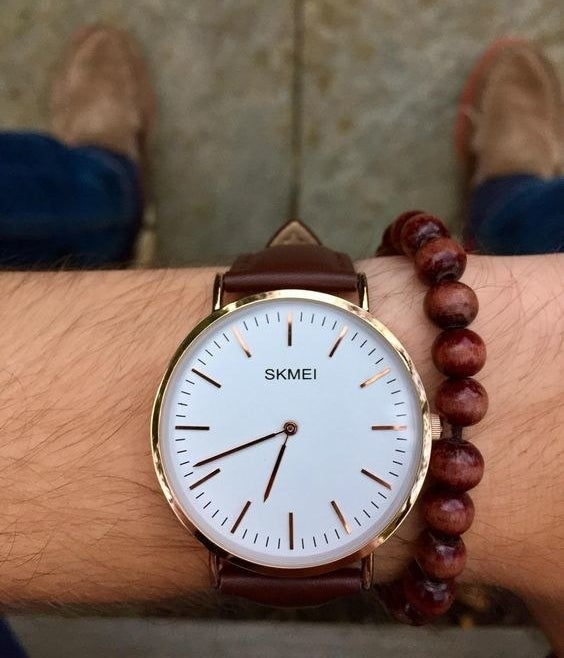 Reviewer wearing the tan watch with a white and gold face