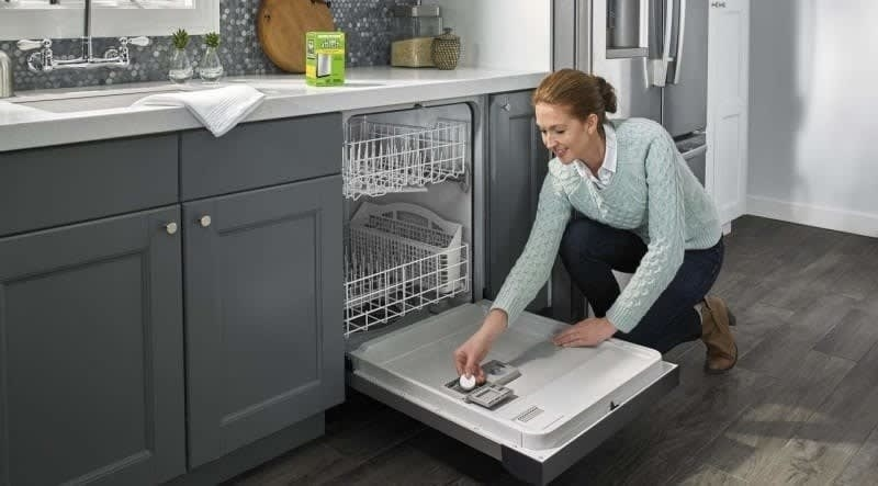 A person putting a cleaning tablet into a dishwasher