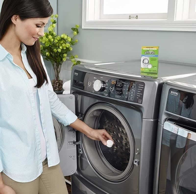 A person putting a cleaning tablet into a washing machine
