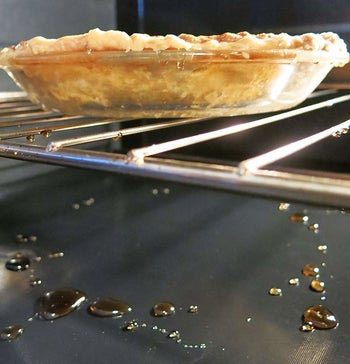 An oven liner catching the remnants of a pie baking inside the oven