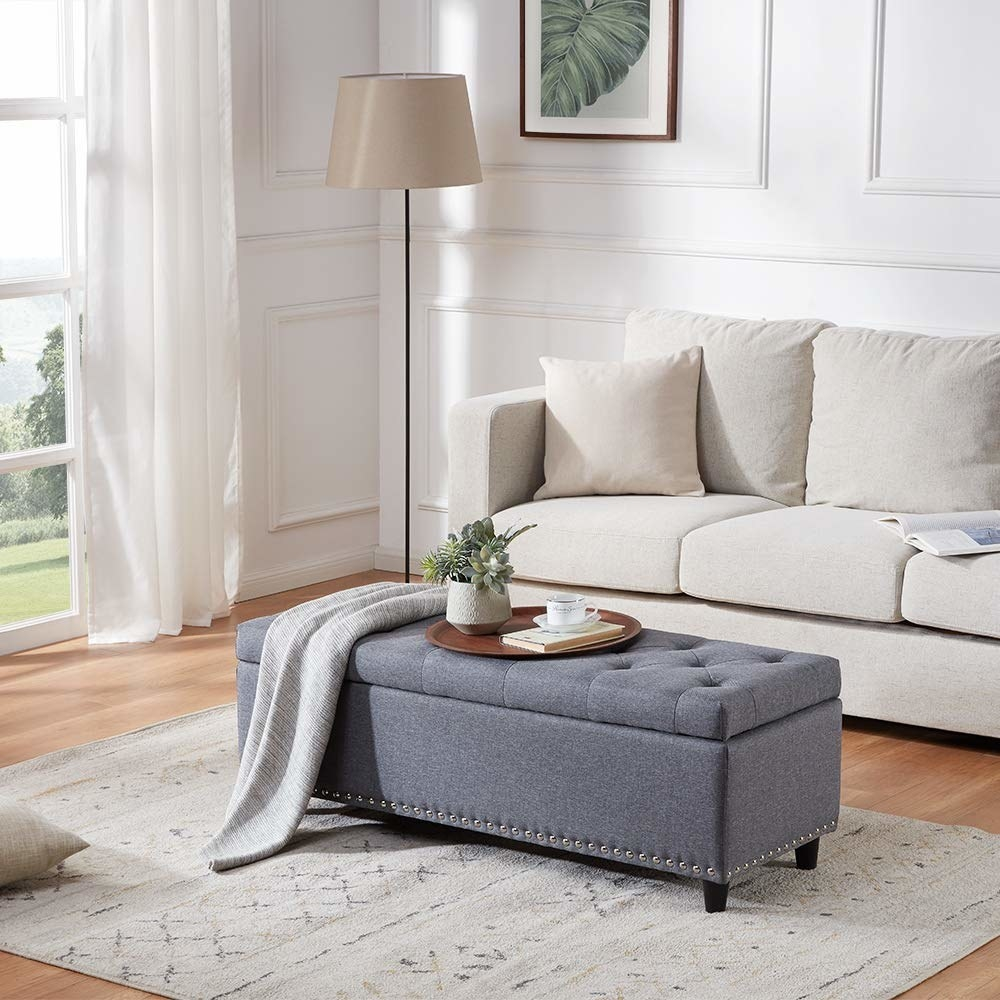 The rectangular ottoman with nailhead trim in grey