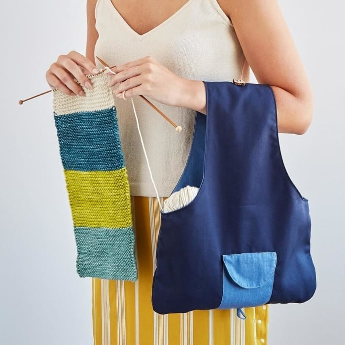 a model knits while holding a tote with yarn in it
