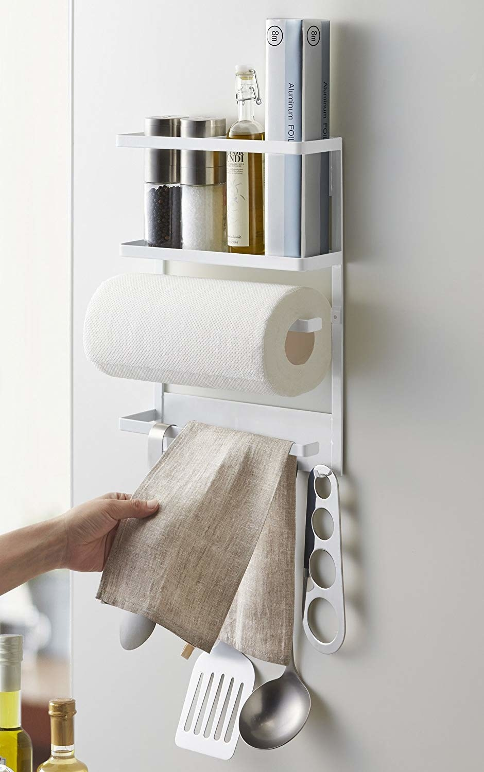 A metal-framed kitchen rack with a top shelf holding books, salt/pepper, and a bottle of oil; a paper towel holder; an arm holding a hand towel; and hooks at the bottom holding utensils like a spatula, ladle, etcetera