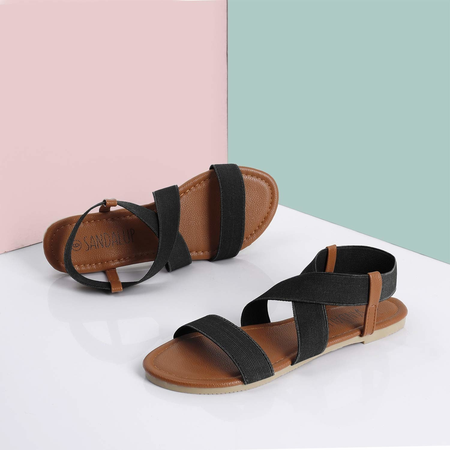 A product shot of the flat sandals showing their faux leather bottom and straps that attach to a curved fabric strap that goes over the top of the foot. There is a two strap in the front with the same fabric.