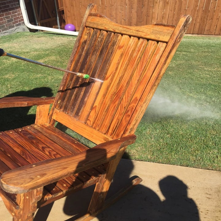 outdoor wooden rocker being pressure washed, half with dark stains, and half where to wood looks like-new