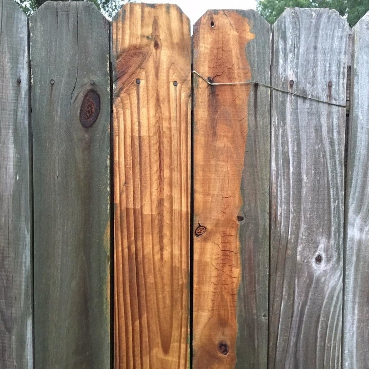 wooden fence that's brown in the middle where it's been pressure washed and grey with residue on either side