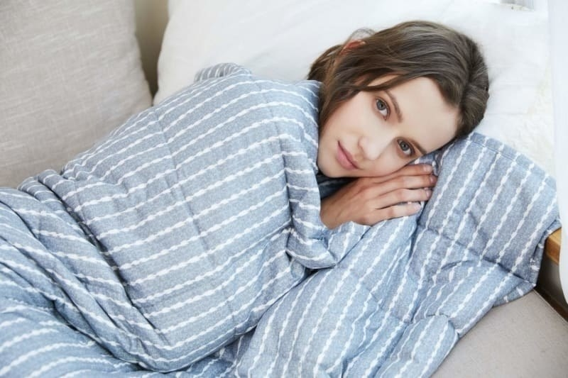Model curled up wrapped in blue weighted blanket with white stripes