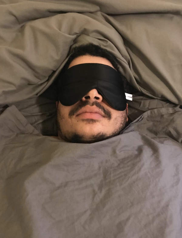 someone laying in bed with the black mask over their eyes