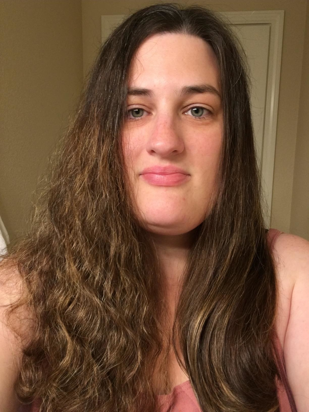 reviewer with half a head of long curly brown hair and half a head of long curly straight hair