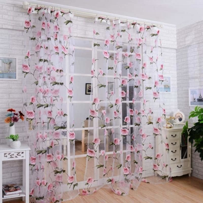 Sheer window treatments with embroidered flowers on them over a window in a room