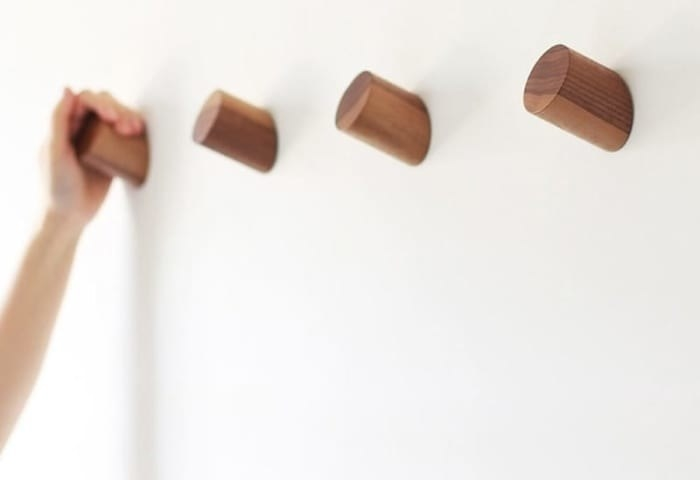 Four simple wood wall hooks with a hand on the farthest one away
