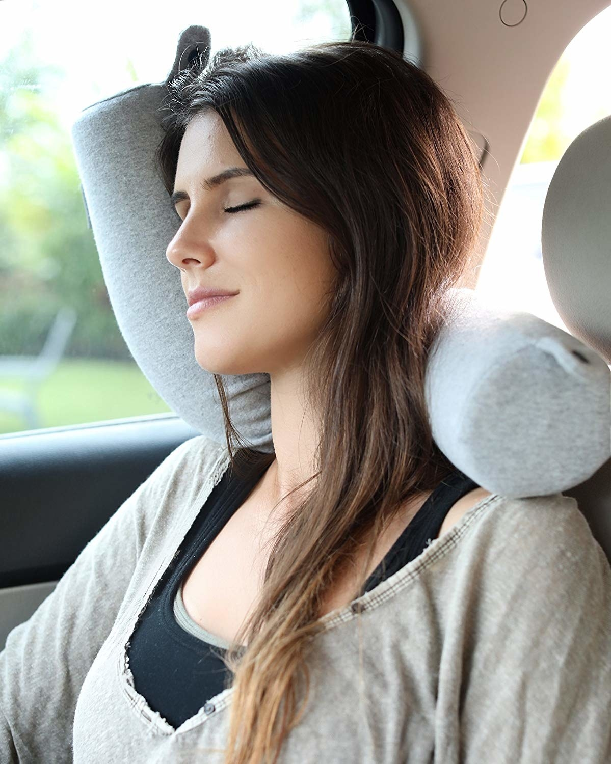 a model sitting in the car comfortably with the pillow wrapped around their neck
