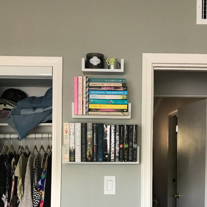 Floating shelves on a wall in between two doorways with the bottom two filled with books and the top with a candle