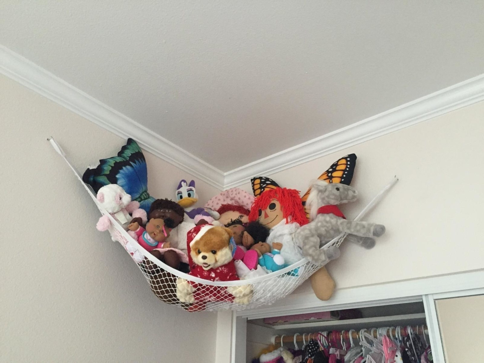 reviewer showing a toy storage hammock in the top corner of their room holding all of their stuffed animals