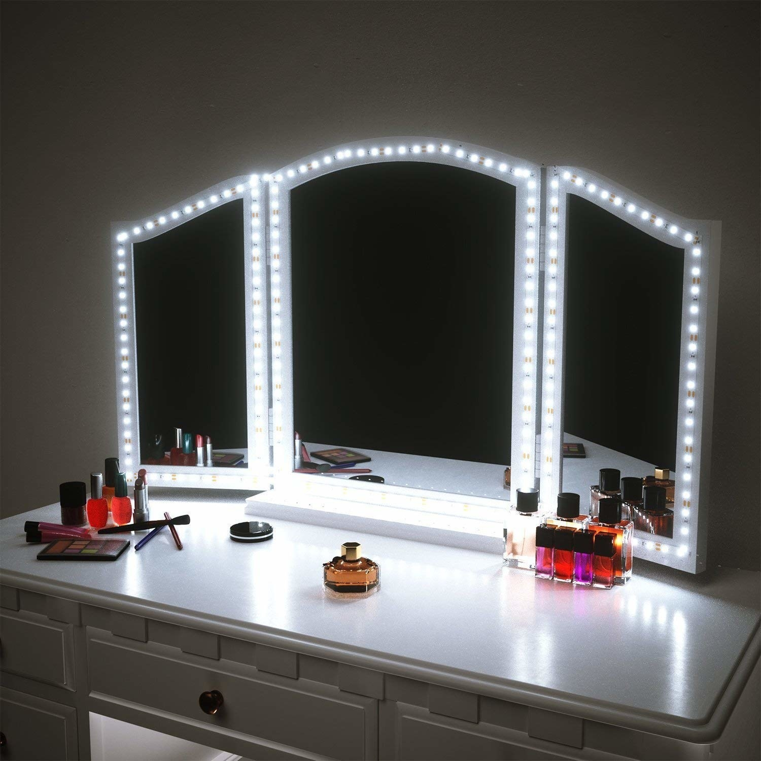 Vanity with a three-section mirror, each with a ring of lights around the outside, illuminating it
