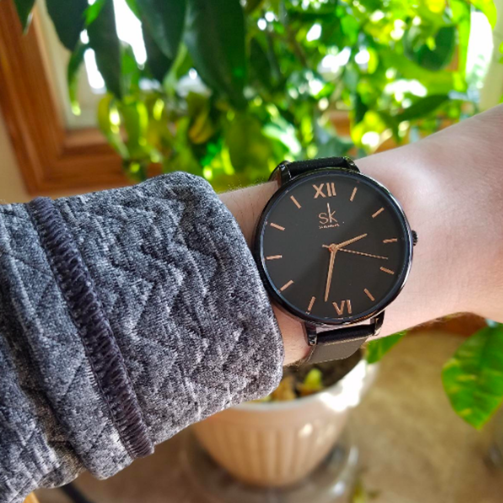 Reviewer wearing the watch in black with gold accents