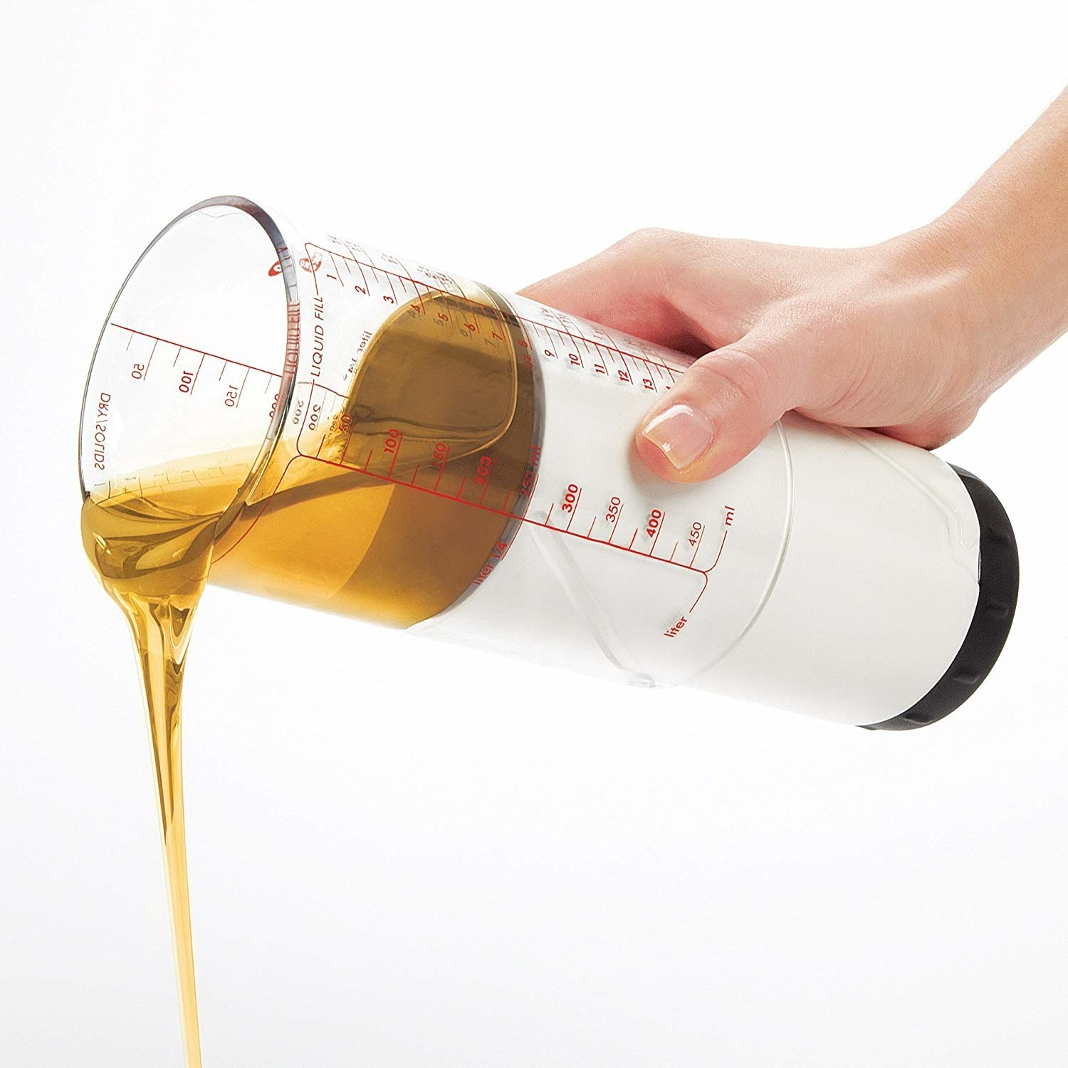 a person using the measuring cup to pour out some oil