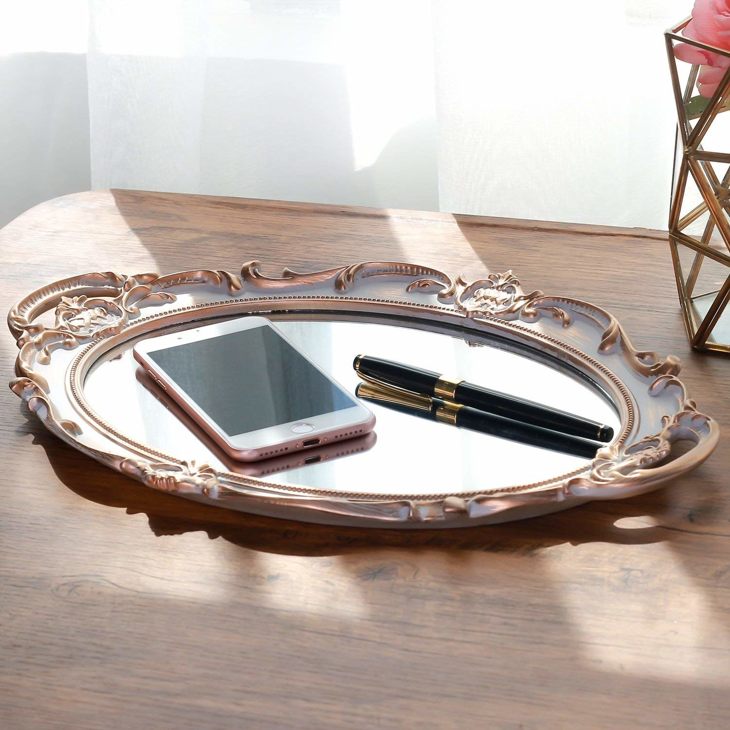 The mirror tray with a phone and a pen on it