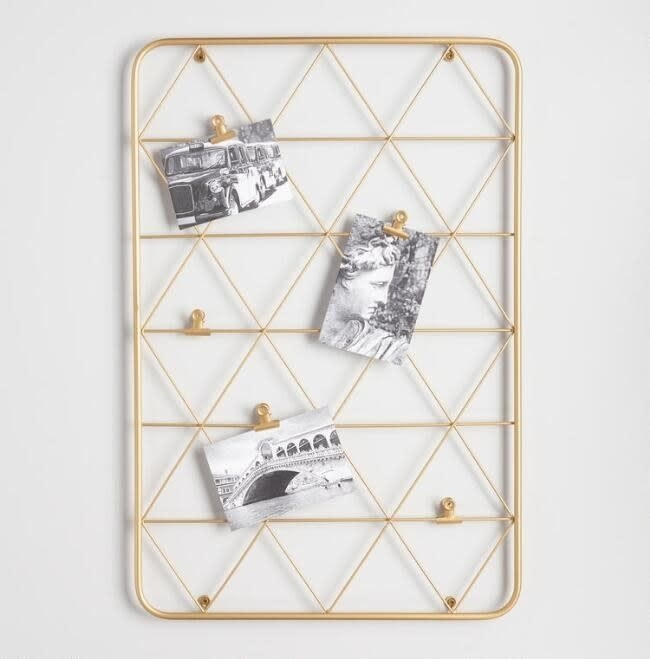 The frame with gold wire triangles with clips holding up three photos