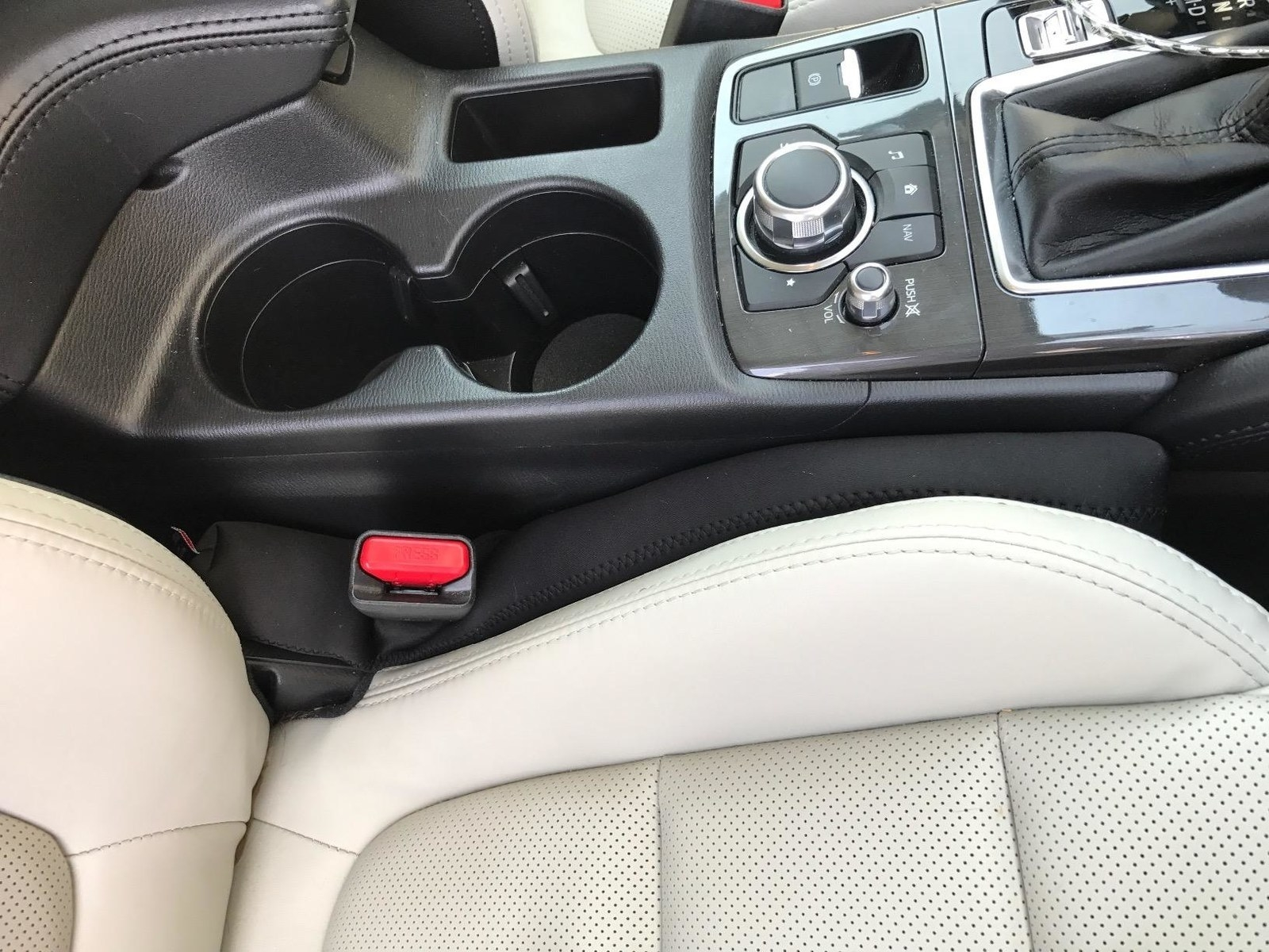 The seat gap filler wedges between a car seat and console