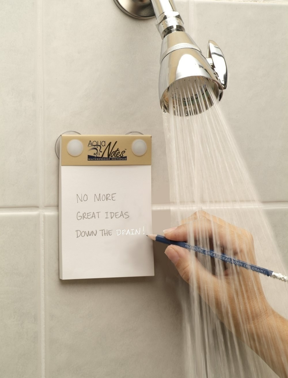 The notepad affixed to a shower wall while a hand writes on it with a pencil