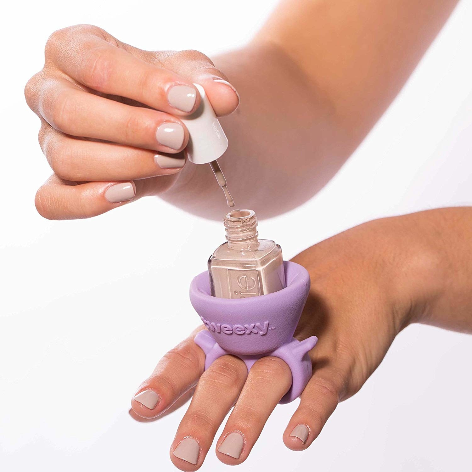 Hands using the ring-like holder to apply nail polish