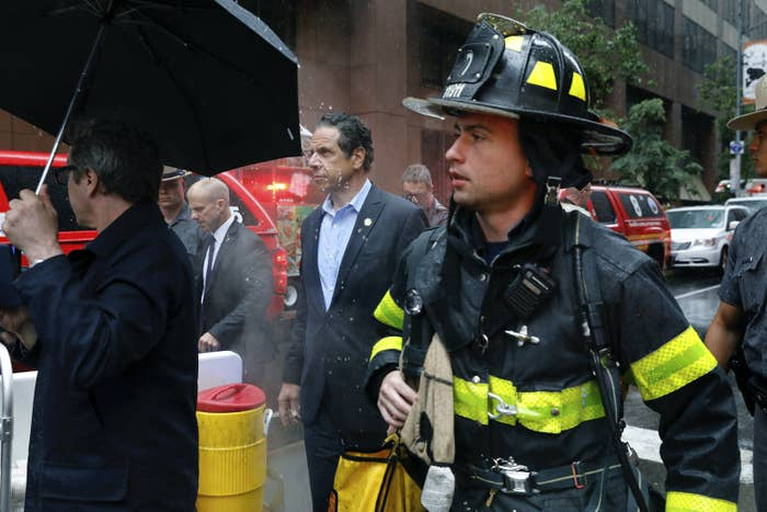 New York Gov. Andrew Cuomo (center) and a firefighter at the scene.