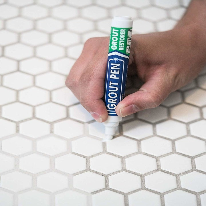 hand holds market and draws white paint over brown grout