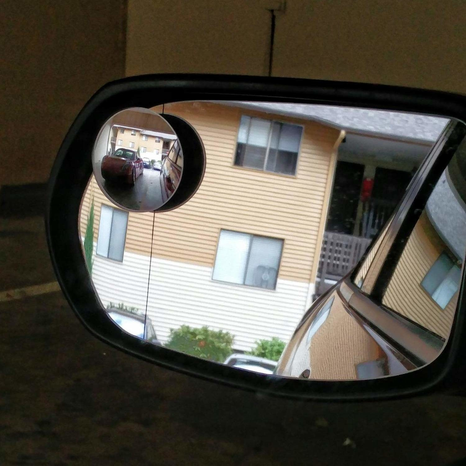 Side mirror of car with circular mirror sticker helping see view behind the car