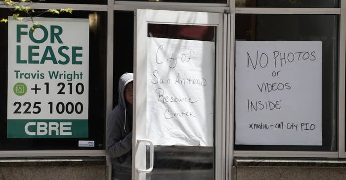 An asylum-seeker peers out the door at a makeshift resource center in downtown San Antonio.