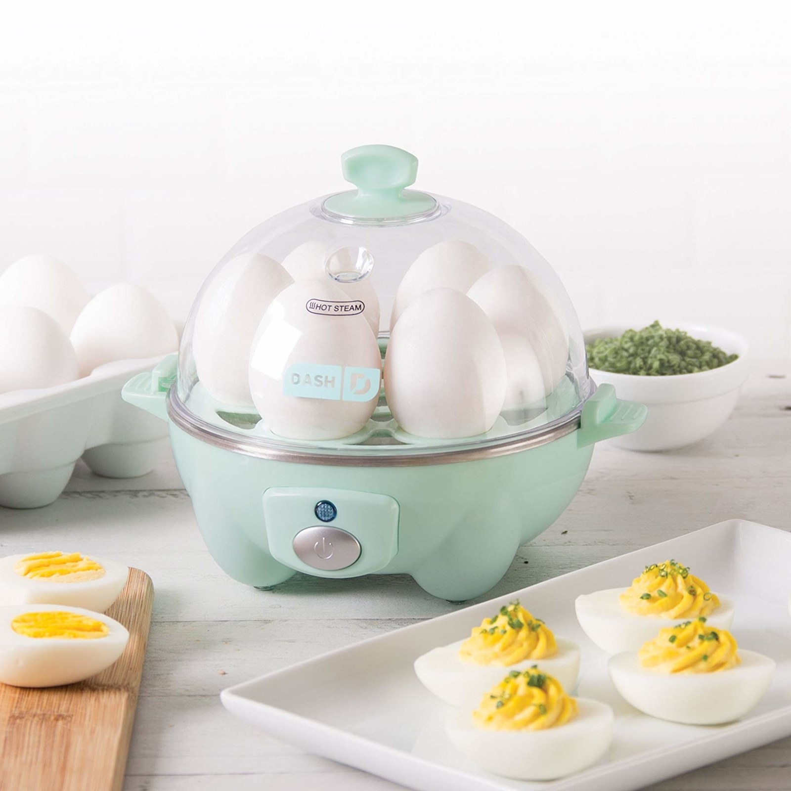 the egg cooker is sitting with six eggs inside of it. Sitting right next to it is a plate of deviled eggs and another boiled egg cut in half